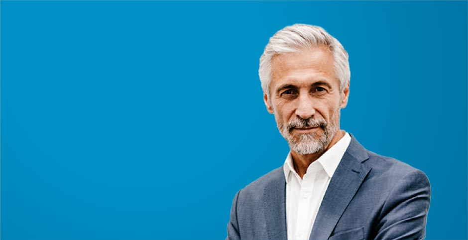 Portrait of a businessman against a blue background.