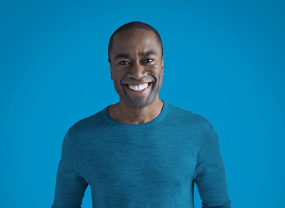 Portrait of smiling man against a blue background.