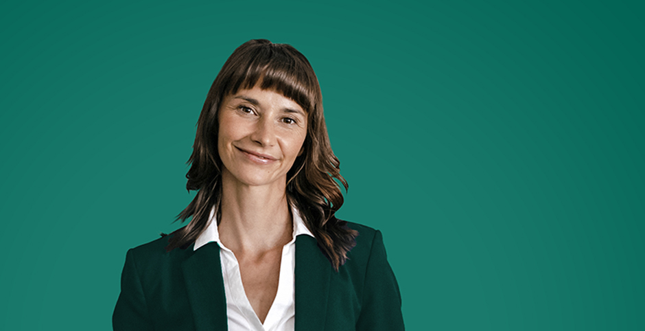 Portrait of a smiling businesswoman against a green background.