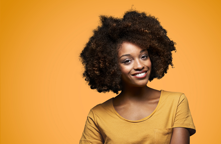 Portrait of woman with curly short hair against orange background.